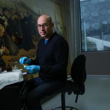 NGV's head of conservation Michael Varcoe-Cocks working on the painting The Pilgrim Fathers.CREDIT:SIMON SCHLUTER